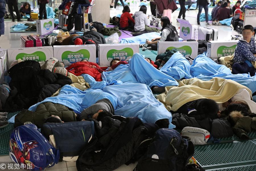 韩国机场航班因降雪延误 乘客席地而睡