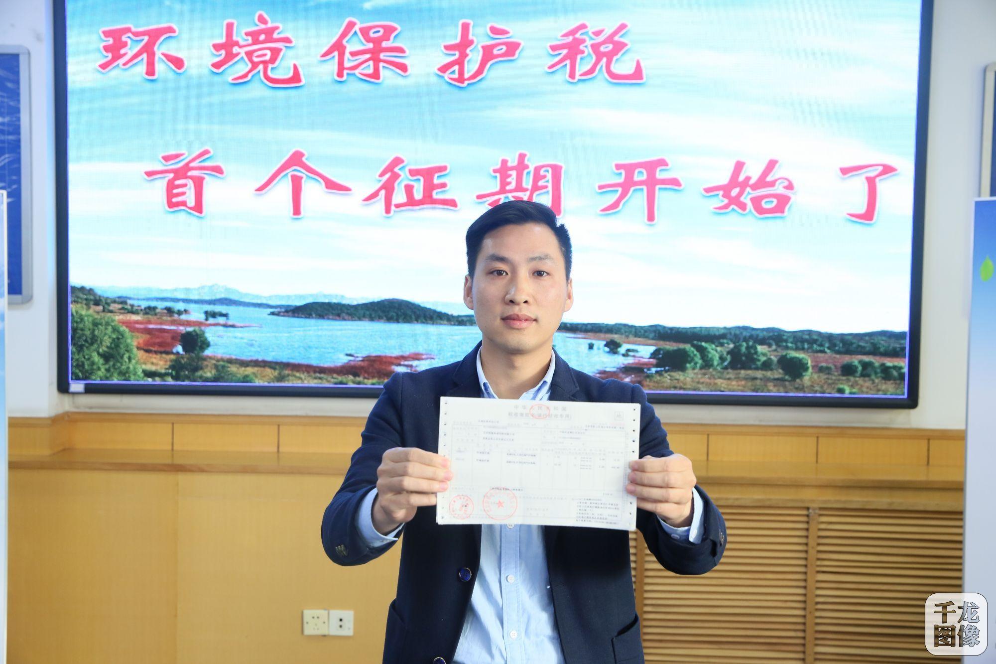 北京特驱希望饲料有限公司财务负责人王虎展示北京市首张环境保护税缴款书