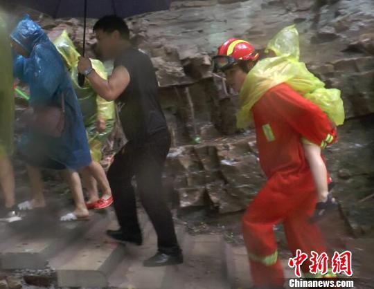 疏导中消防人员背着孩子前进 消防供图 摄