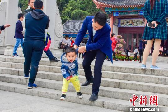 图为一名父亲带着儿子在广东罗浮山游玩,十分惬意。 刘艳如 摄