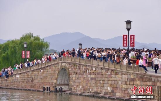 资料图:国庆长假,大量游客涌入西湖断桥。<a target=&#39;_blank&#39; href=&#39;http://www.chinanews.com/&#39;>中新社</a>记者 李晨韵 摄