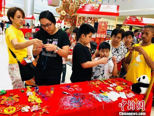 图为菲律宾孩童学习编制中国结。 樊蓉 摄