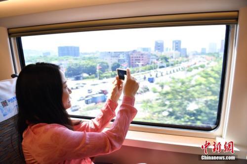 """图为""""复兴号""""高铁旅客拿手机拍摄窗外景色。 <a target=&#39;_blank&#39; href=&#39;http://www.chinanews.com/&#39;>中新社</a>记者 陈文 摄"""