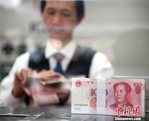 11月23日,中国外汇交易中心发布数据,人民币对美元汇率中间价报6.6021,较前一交易日大幅上涨269个基点。图为广西南宁一银行工作人员清点货币。(资料图片)<a target=&#39;_blank&#39; href=&#39;http://www.chinanews.com/&#39;>中新社</a>记者 俞靖 摄