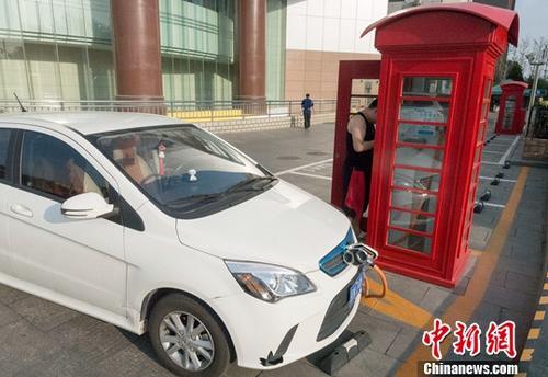 6月10日,北京,一位电动汽车车主正操作充电桩给车辆充电,该充电桩的外观被设计成类似英国伦敦街头的经典红色公用电话亭,别具特色。<a target=&#39;_blank&#39; href=&#39;http://www.chinanews.com/&#39;></a>中新社</a>记者 侯宇 摄