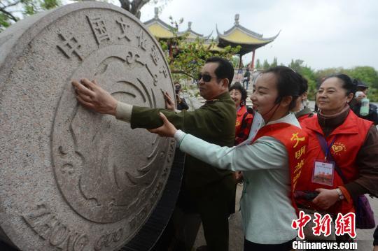 图为盲人触摸廋西湖景区里的中国文化遗产标志。 孟德龙 摄