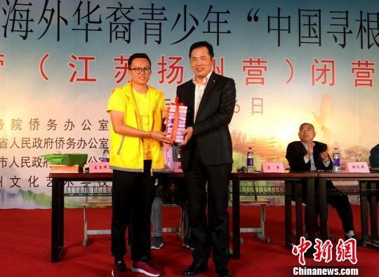 图为扬州市政府副秘书长吴军(右)在闭营仪式上与春令营领队老师互赠礼品。  王爱萍 摄