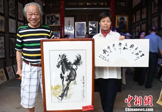 参展老艺术家、福州市原常务副市长龚雄(左)与专程前来认捐其画作献爱心的企业代表合影。 记者刘可耕 摄