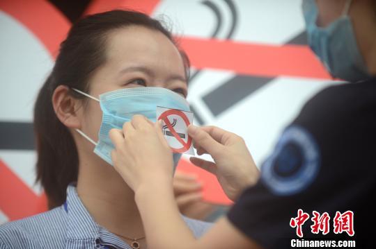 图为佩戴禁烟标志口罩的志愿者走上街头禁烟。 孟德龙 摄