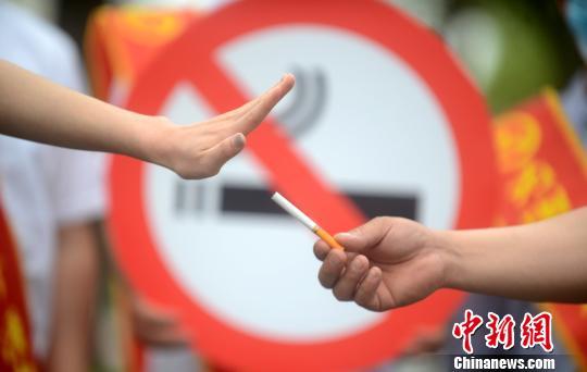 图为控烟志愿者在街头用行为艺术劝市民戒烟。 孟德龙 摄
