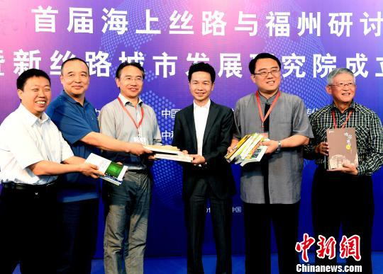 """两岸专家学者向该研讨会上揭牌成立的""""海上丝绸之路文献馆""""赠书。 记者刘可耕 摄"""