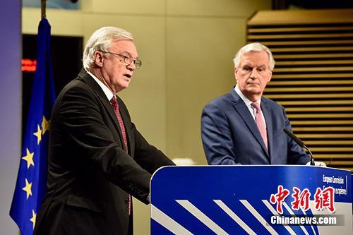"""当地时间3月19日,脱欧谈判欧盟首席谈判代表巴尼耶(图右)与英国脱欧事务大臣戴维斯(图左)共见记者,宣布双方迈出""""决定性一步"""",就脱欧过渡期安排等议题达成协议,但棘手的英国北爱尔兰与爱尔兰边界问题仍悬而未决。 欧盟供图"""