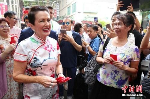 2月5日,中国农历新年大年初一,悉尼市长克罗芙·摩尔(左)到唐人街拜年,与商户和游人共庆中国新年。图为摩尔向游人派发利是红包。