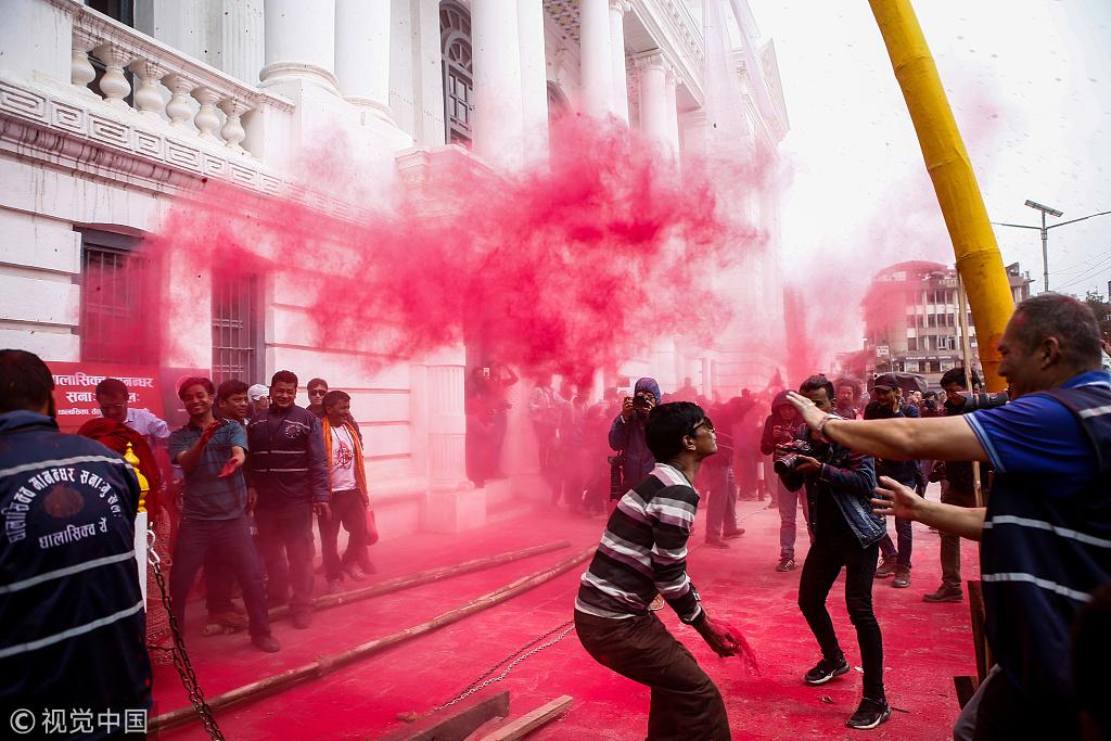 尼泊尔举行洒红节 民众狂撒朱砂红烟四起