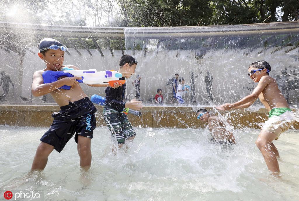 日本民众战高温:儿童扎堆玩水 女性带小风扇出门