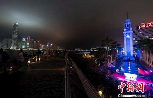 资料图片:香港尖沙咀钟楼亮灯。图为蓝色钟楼与维多利亚港的迷人夜景交相辉映。