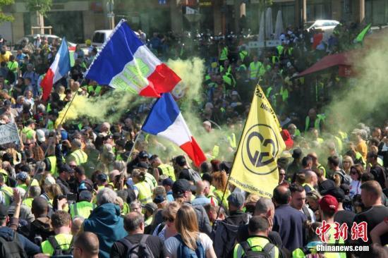 资料图:当地时间2019年4月20日,巴黎再次发生大规模示威,并伴随暴力冲突。巴黎圣母院本周遭遇的大火,未能阻挡示威者的步伐,有9000人参与当天的示威。数千名示威者在贝尔西车站集合,有人不断施放黄色烟雾,气味浓烈。