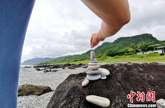 旅客玩海边石头。 钟欣 摄