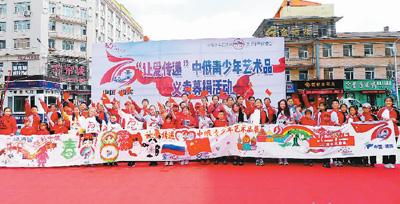 图为2019年5月11日,中俄青少年挥舞国旗展示10米友谊长卷。邱齐龙摄(人民视觉)