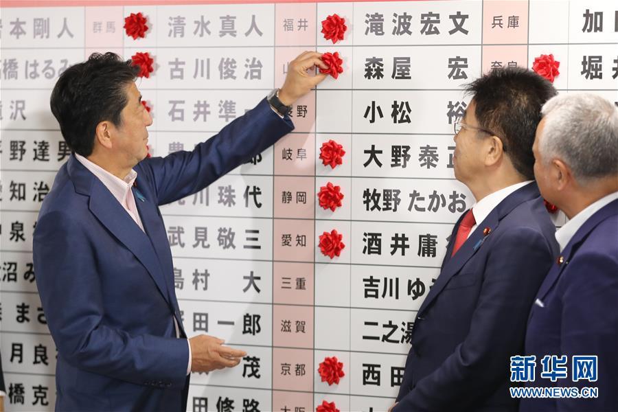 7月21日,在日本东京自民党总部,日本首相、自民党总裁安倍晋三(左)为预测当选的自民党议员贴红花。.jpg