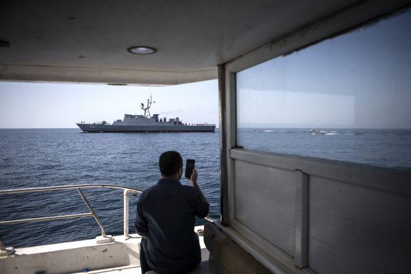 资料图片:2019年4月30天,同样名男子用手机拍摄在霍尔木兹海峡巡逻的伊朗军舰。新华社发