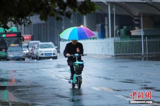 资料图:市民冒雨出行。<a target='_blank' href='http://www.chinanews.com/'>中新社</a>记者 王中举 摄