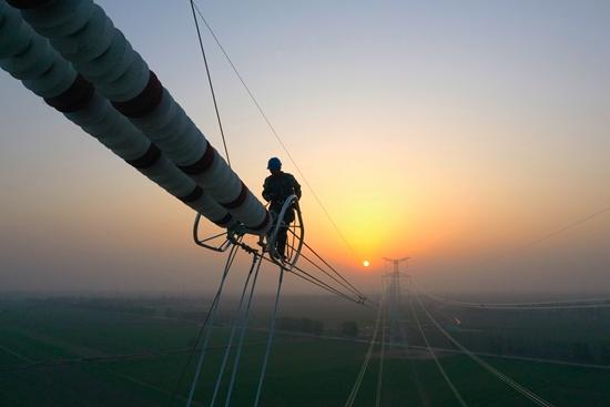 夕阳下,工人正在安装铁塔均压环.jpg