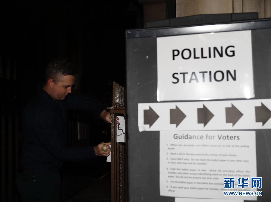 12月12日,在英国伦敦,一名工作人员在一个投票站准备。 英国议会下院选举于当地时间12日上午7时开始投票。 .jpg