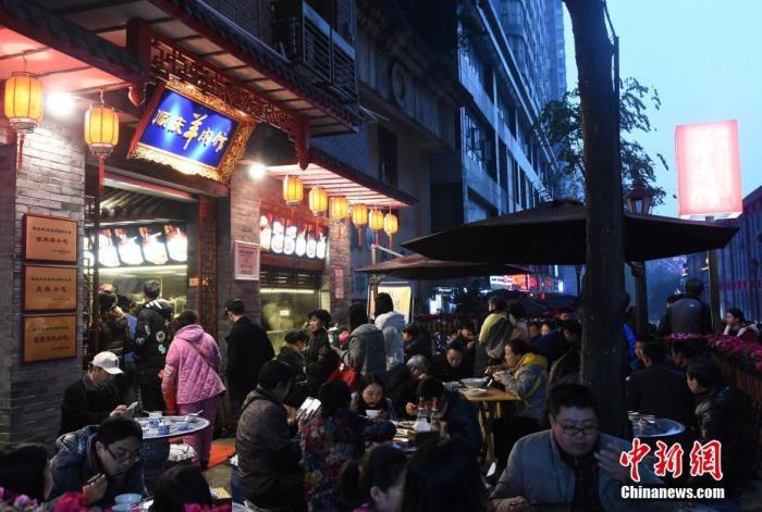 """资料图:12月21日是中国传统节气——冬至。当日,记者走访重庆多家羊肉馆看到,店内生意火爆,有的店家甚至把场地从室内扩大到室外,搭建起临时营业点,场面如""""坝坝宴""""。 周毅 摄"""