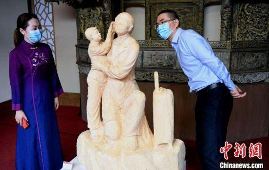 参展木雕作品《疫不容辞》吸睛。 记者刘可耕 摄