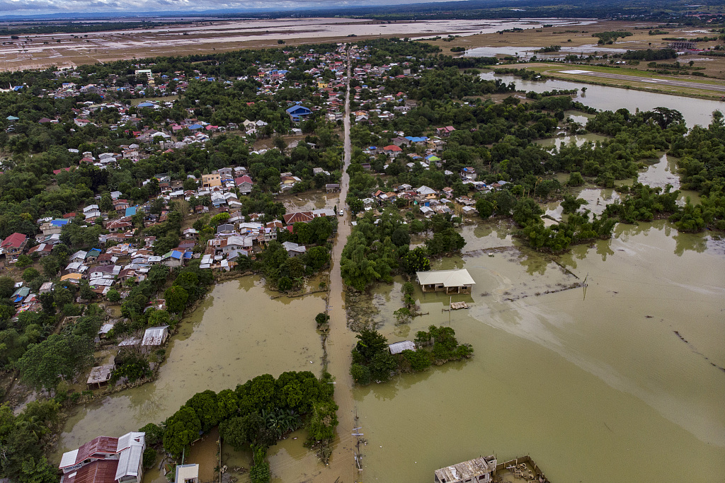菲律宾民众返回受灾地区 在洪水中排长队领救援物资