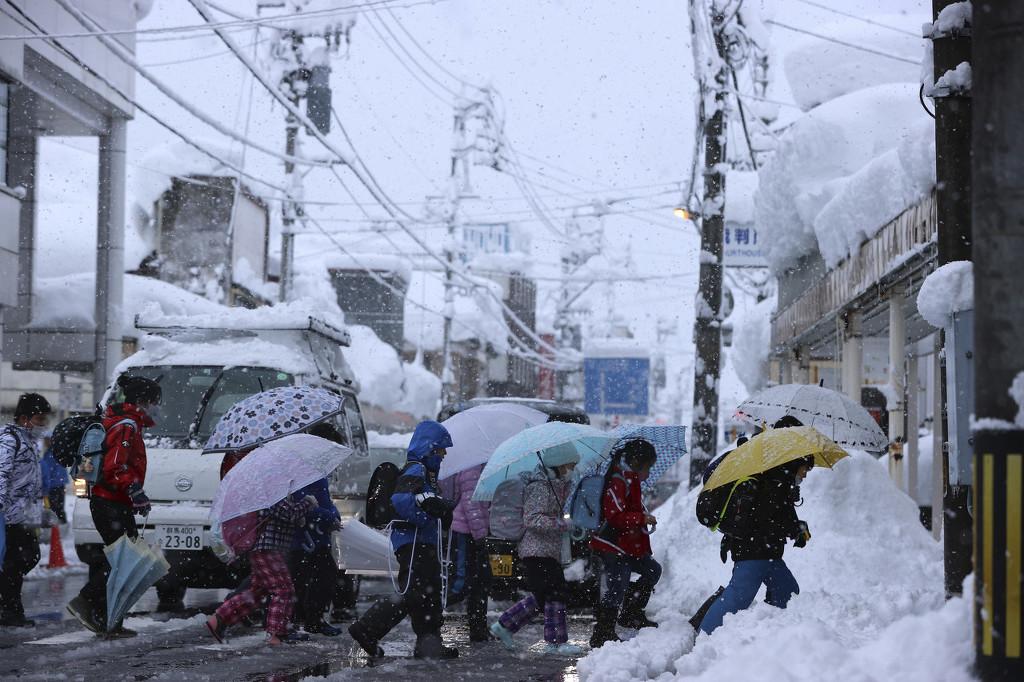 日本新潟县持续降雪 儿童撑伞排路队上学