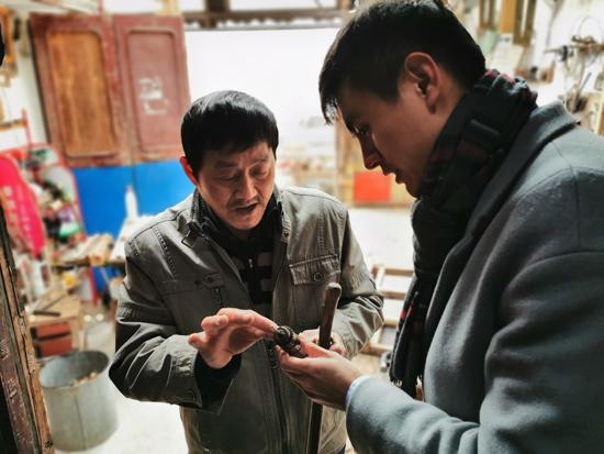 """唐木杰:民间艺人,古城""""木痴""""在向工作人员介绍他的创新砖头"""