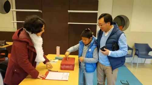 家长与孩子一起在学校捐赠(中国华文教育基金会 供图)