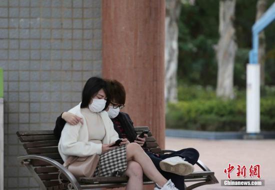"""资料图:""""新冠疫情""""下的香港周日,戴上口罩一对情侣在公园安坐休息。 <a target='_blank' href='http://www.chinanews.com/'>中新社</a>记者 洪少葵 摄"""