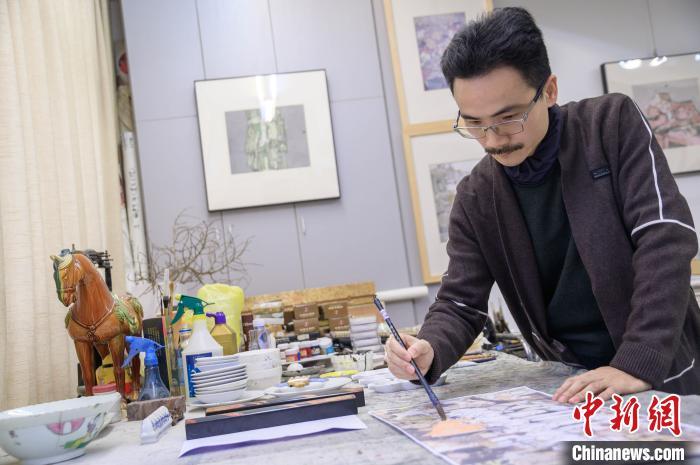 图为翁志承在为抗疫系列的画作进行润色。 李南轩 摄