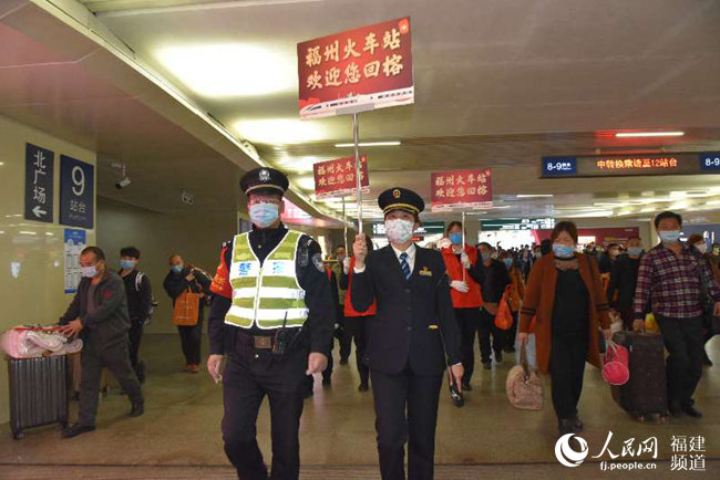 福州火车站党团员青年突击队和值班铁路民警引导旅客出站。 江曲摄