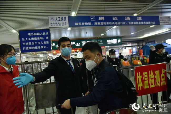 福州火车站客运工作人员正在引导旅客测温。江曲摄