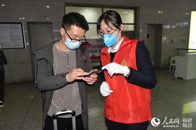 """福州火车站党团员青年突击队员指导湖北籍旅客填报""""e防控""""。 江曲摄"""