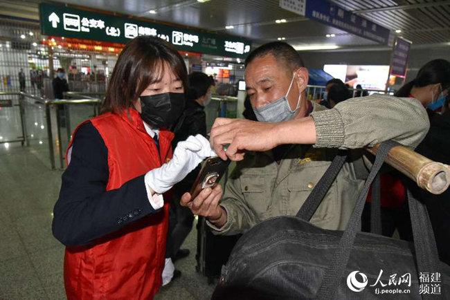 """福州火车站党团员青年突击队员指导湖北籍旅客填报""""e防控""""。江曲摄"""