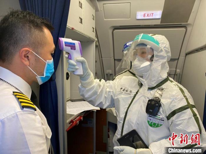图为兰州中川机场海关工作人员对机组人员开展体温筛查。 杨冰玉 摄