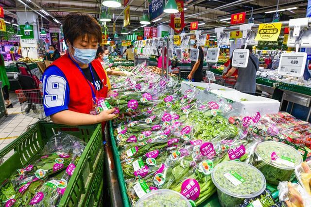 6月14日,北京一家超市工作人员正在对蔬菜货架进行补货。(图源:北京日报客户端)_副本.jpg