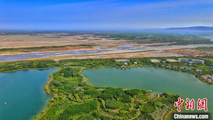 航拍夏日甘肃戈壁小城:半边湖水半边城