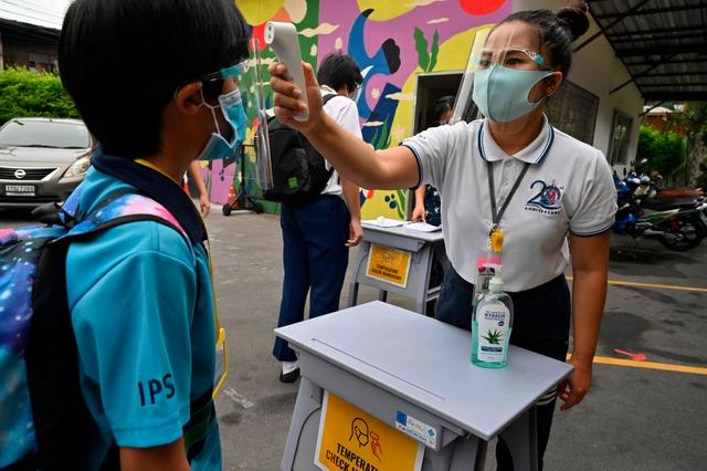 6月16日,在泰国曼谷,学校工作人员为一名学生检测体温。.jpg