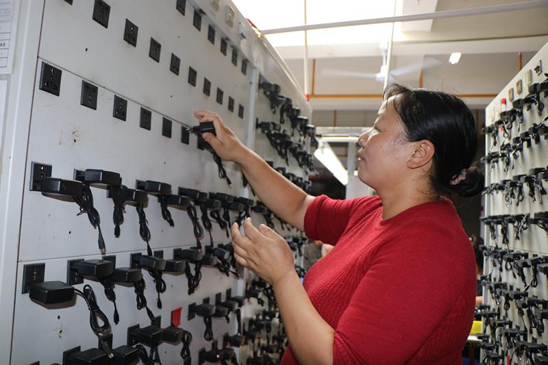 7月3日,在保山大华海瀚科技有限公司第一扶贫车间,李晓艳检测组装后的充电器.JPG