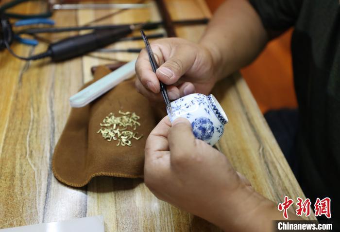 张兵正在为瓷器嵌入锔钉。 于晶 摄