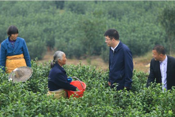 上乐村驻村第一书记周臻杨正在与工作的贫困户进行交流