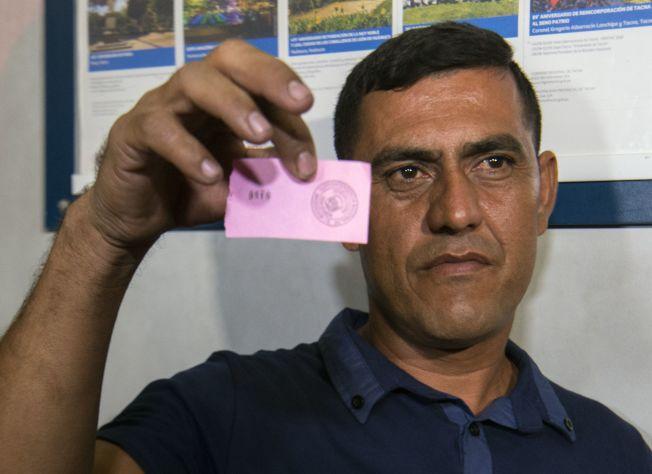 一委国男子拿到号码牌,意味着他可获准进入秘鲁。