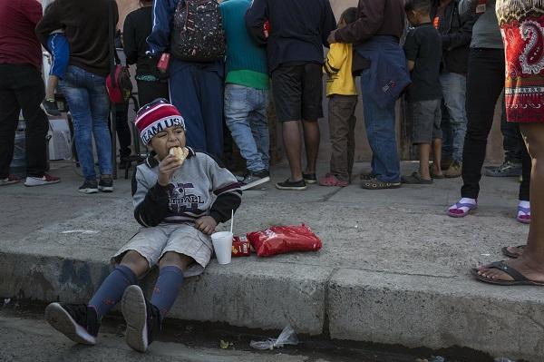 来自中美洲的移民儿童坐在路边啃食面包