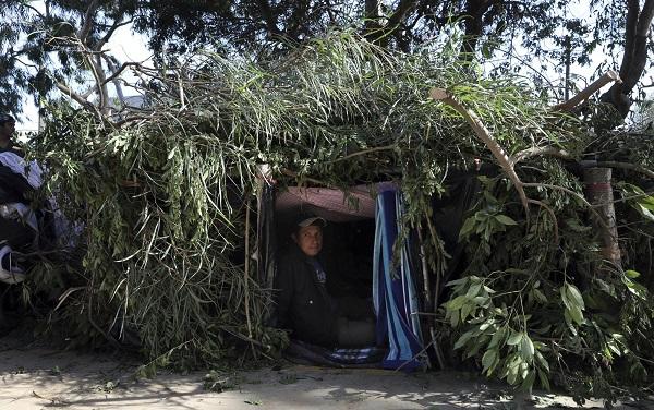 一名移民正在搭好的简陋帐篷中休息